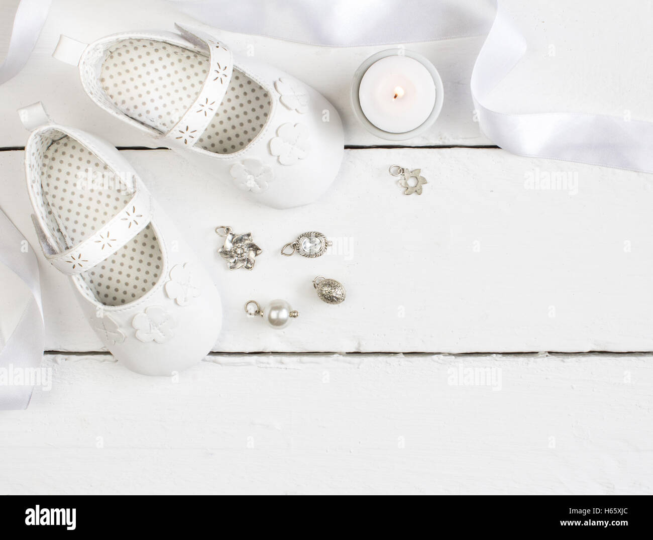 Overhead photo of pair of white baby booties, candle, ribbon and charms on white painted table - Stock Image