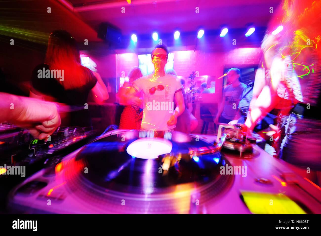 DJ behind the decks in a nightclub. - Stock Image