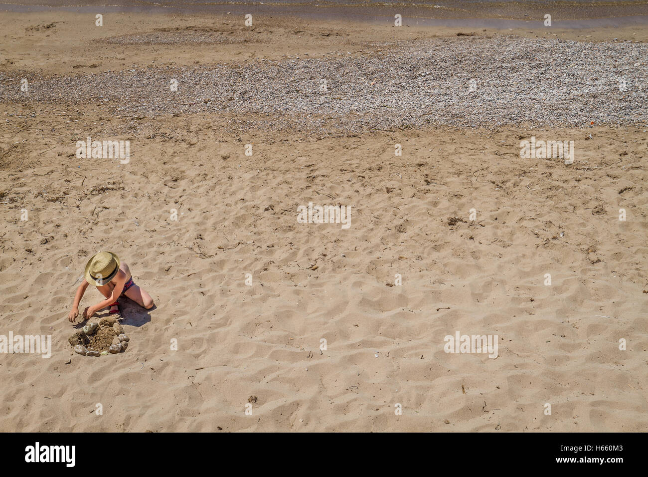young lad playing with stones and sand on beach on sunny day - Stock Image