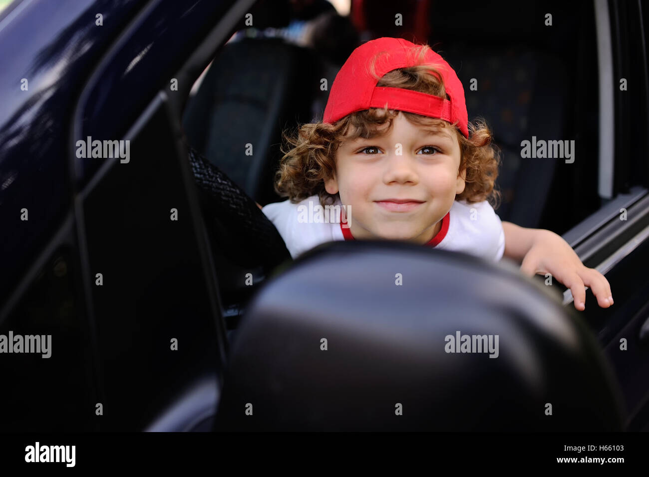 906cf4d21 child with curly hair and a red cap sits behind the wheel of car ...