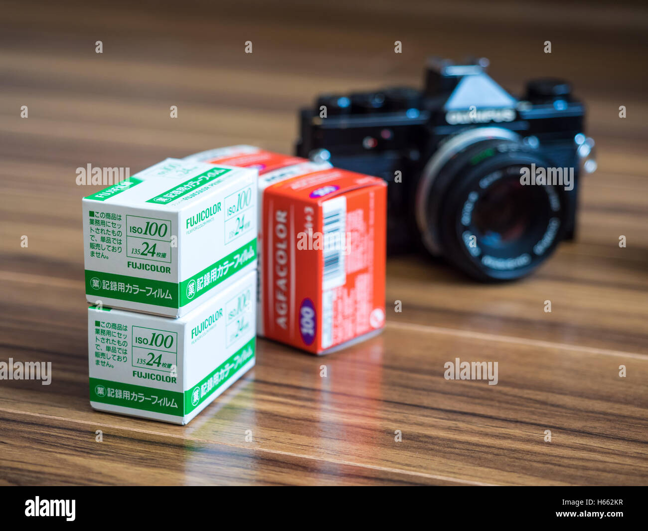Analogue Photography. Fujicolor and Agfacolor 35mm film rolls and old Olympus SLR film camera. - Stock Image