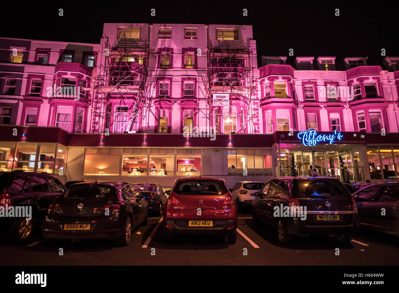 Brightly lit, magenta pink hotel in Blackpool, England during autumn while the famous Black Illuminations are lit up Stock Photo