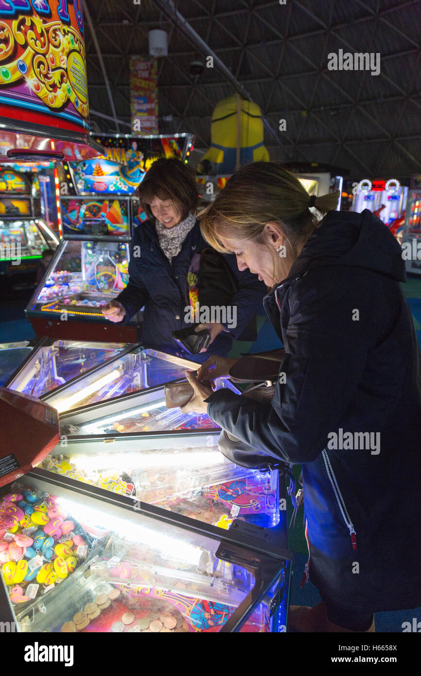 Adults playing in the amusement arcade, Brighton Pier, Brighton, East Sussex England UK - Stock Image