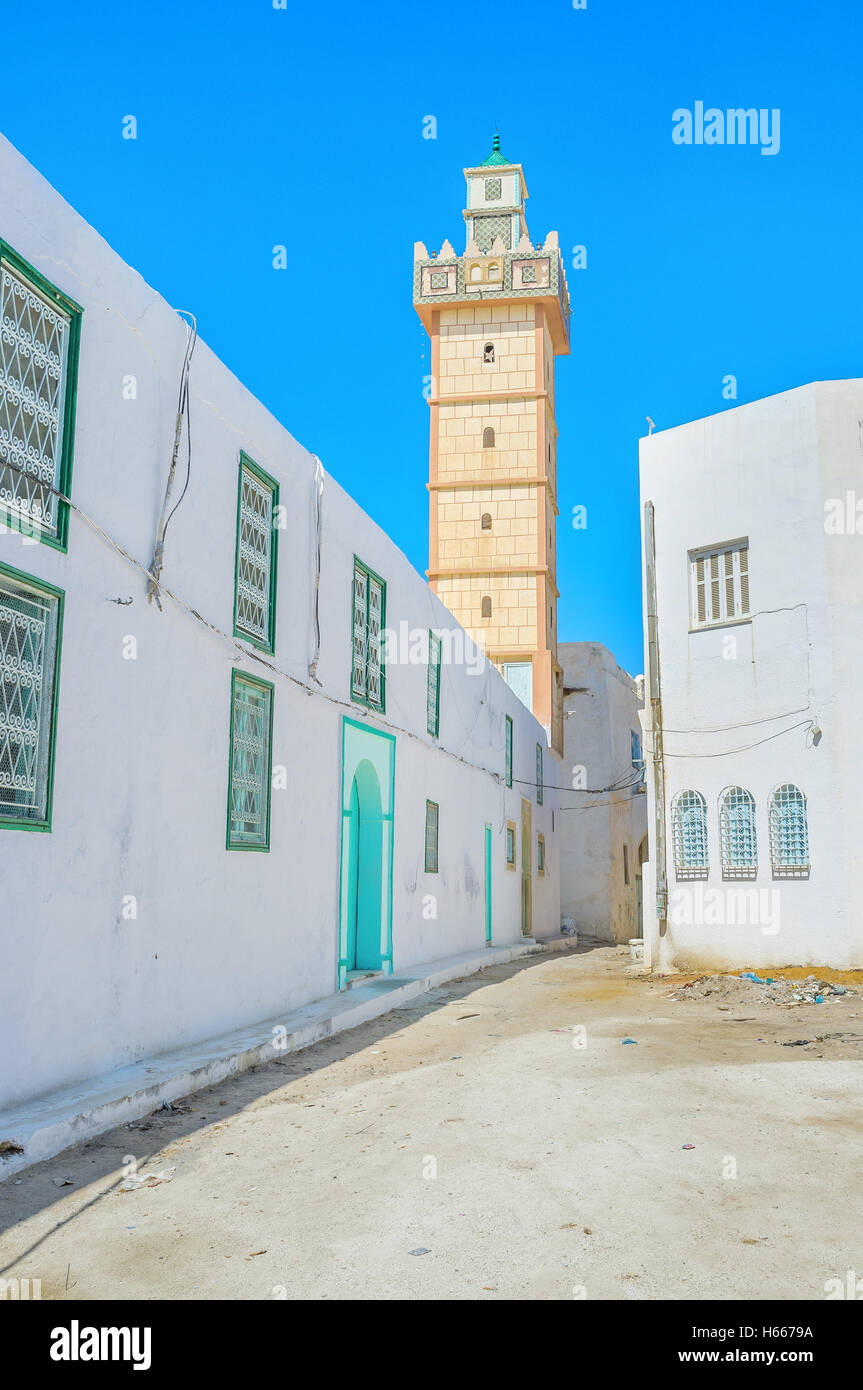 The narrow street with the white houses and high minaret covered with yellow tiles, Kairouan, Tunisia. - Stock Image