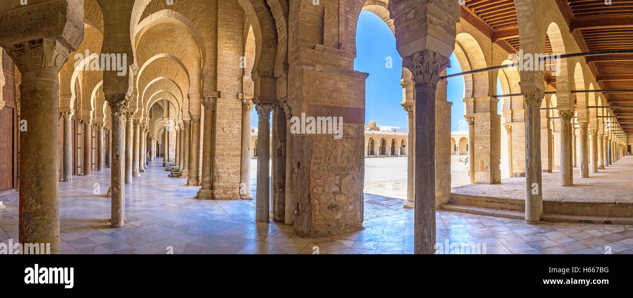 The medieval shady covered terrace of the Grand Mosque consists of many raws of columns that support the arches - Stock Image