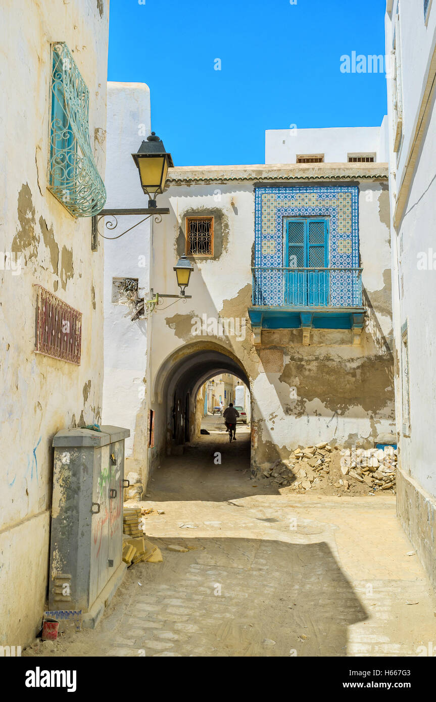 The old house across the street has the narrow passage, Kairouan, Tunisia. - Stock Image