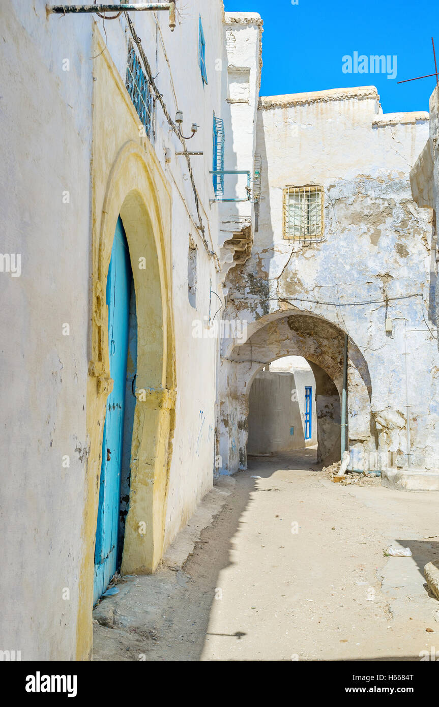 The narrow backstreet with the passage through the residential house, Kairouan, Tunisia. - Stock Image