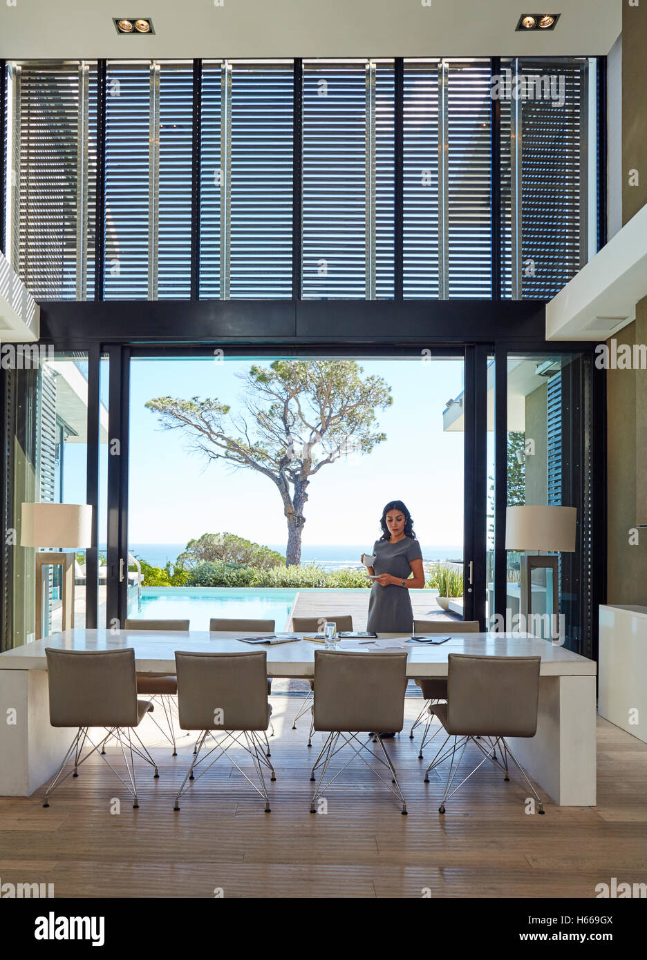 Businesswoman working at dining table in luxury home showcase interior - Stock Image