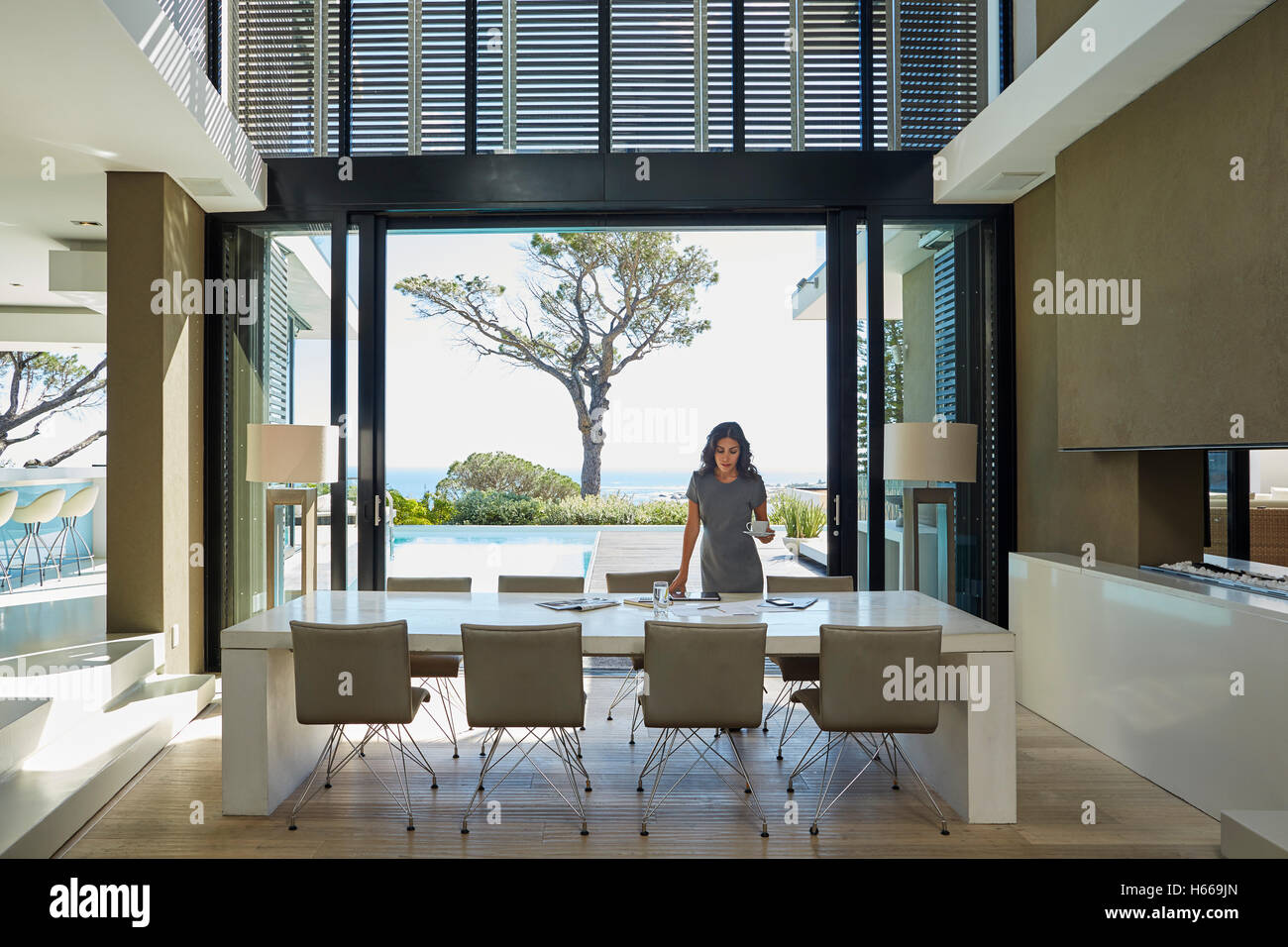 Businesswoman working at dining table in home showcase interior - Stock Image