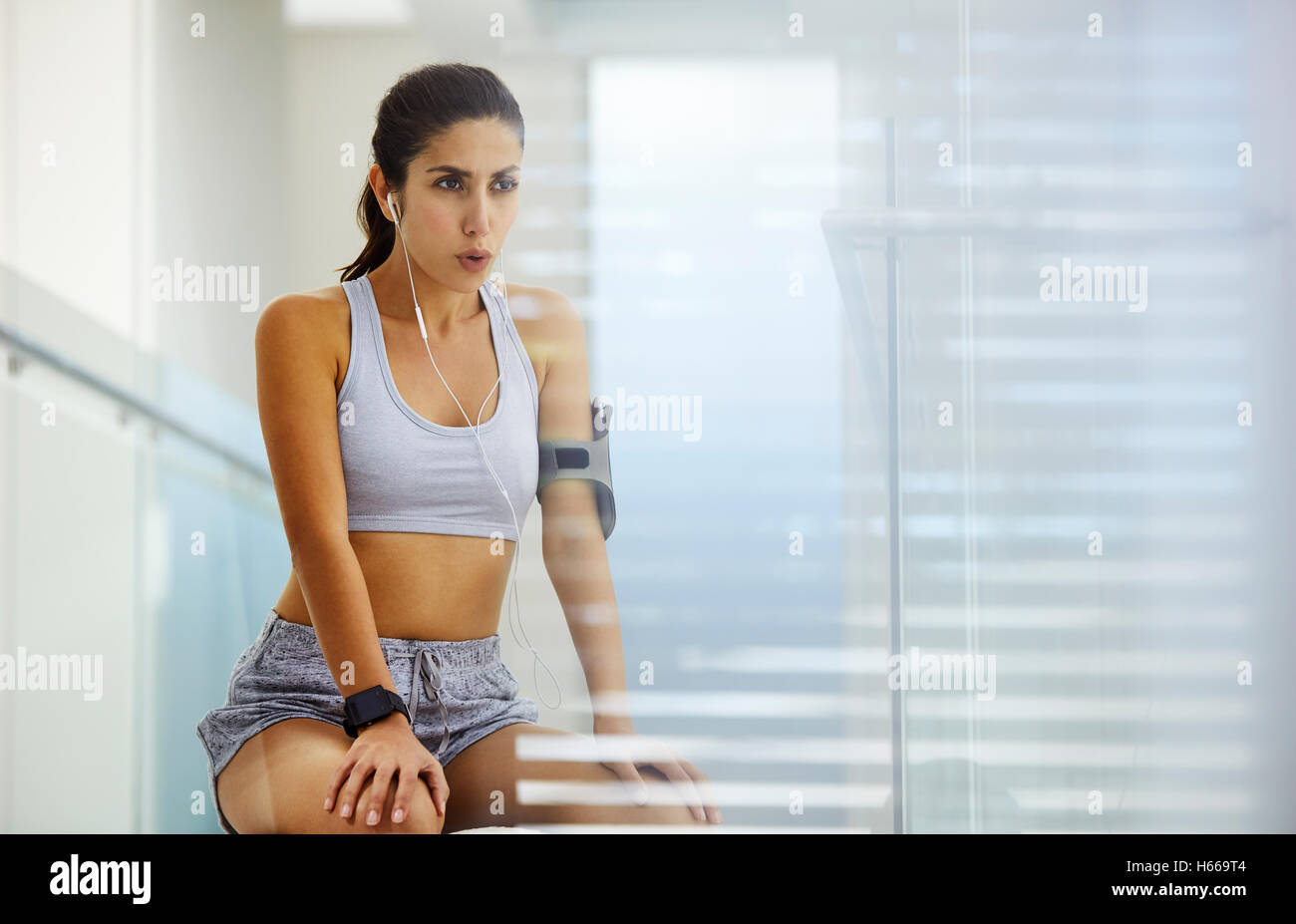 Woman in sports bra and shorts resting listening to music with headphones post workout Stock Photo