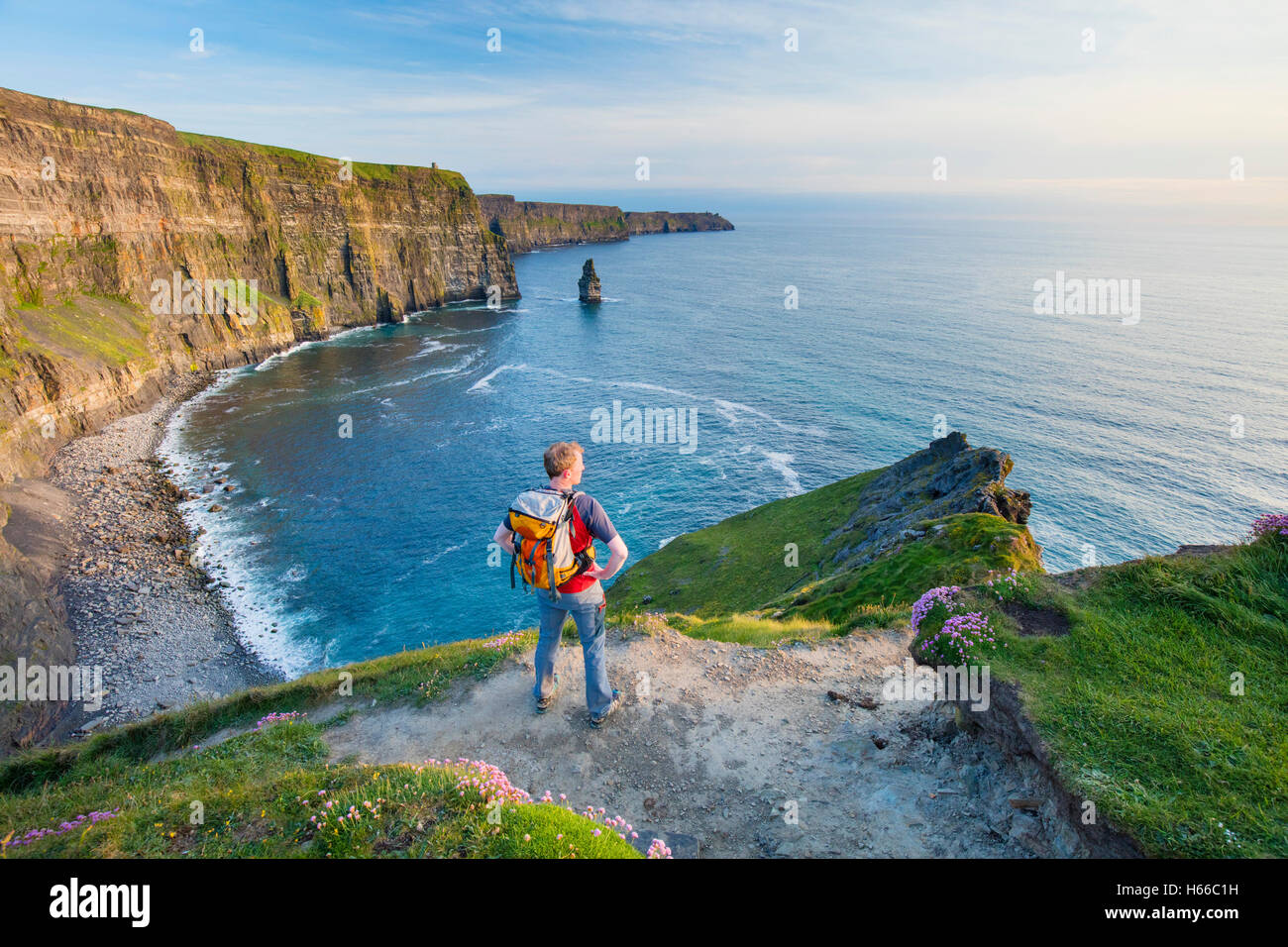 Walker at the Cliffs of Moher, County Clare, Ireland. - Stock Image