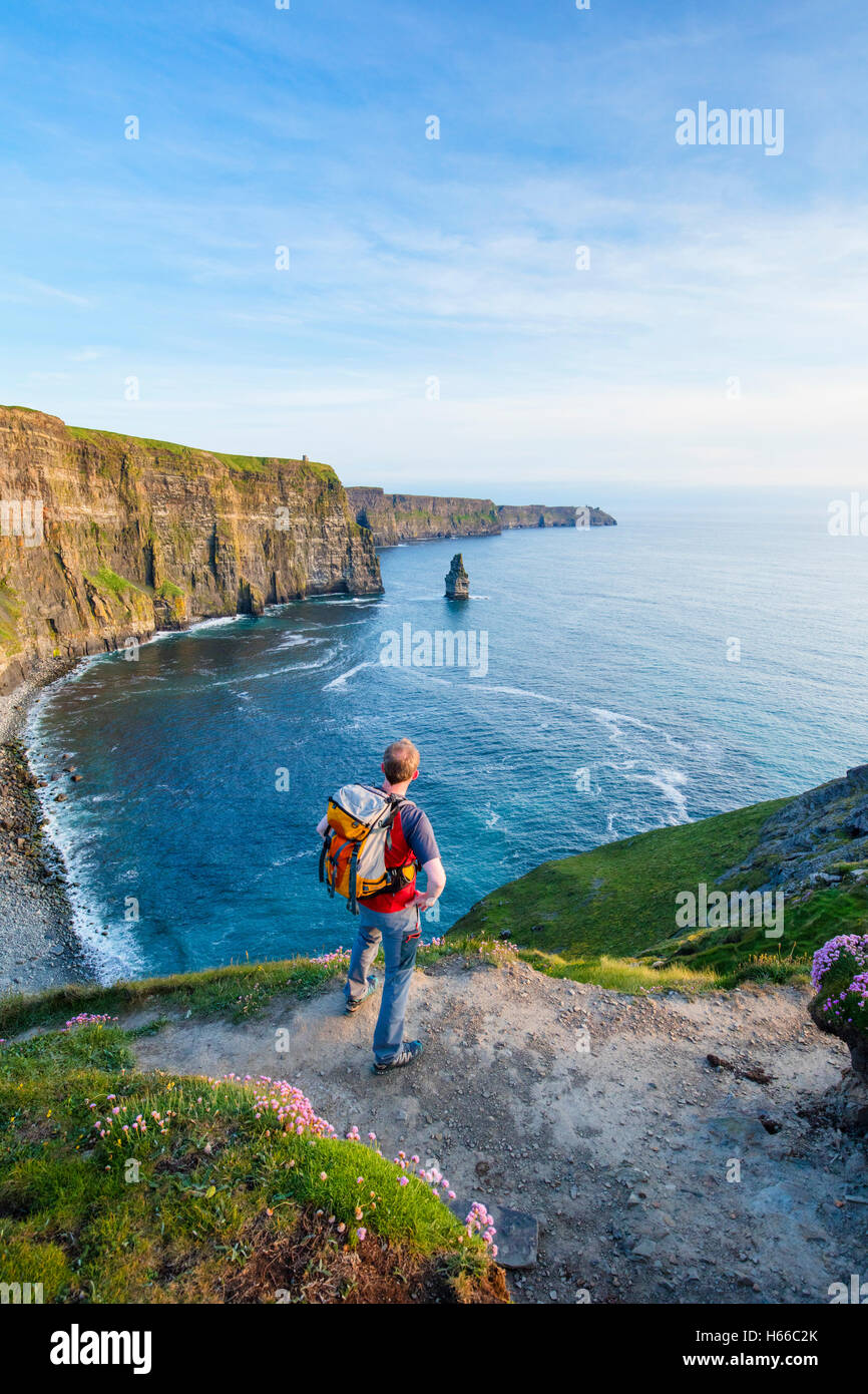 Hiker looking across the Cliffs of Moher, County Clare, Ireland. - Stock Image
