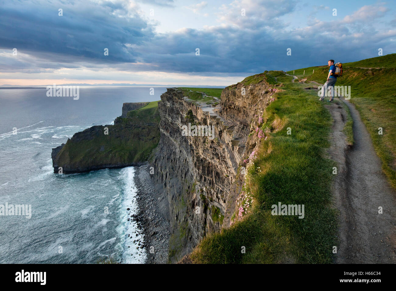 Hiker on top of the Cliffs of Moher, County Clare, Ireland. - Stock Image