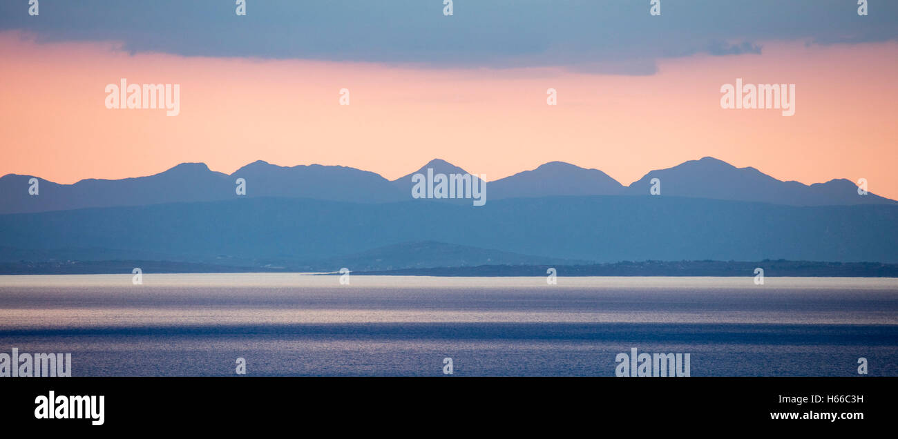 Sunset view of the Twelve Bens rising across Galway Bay, County Clare, Ireland. - Stock Image