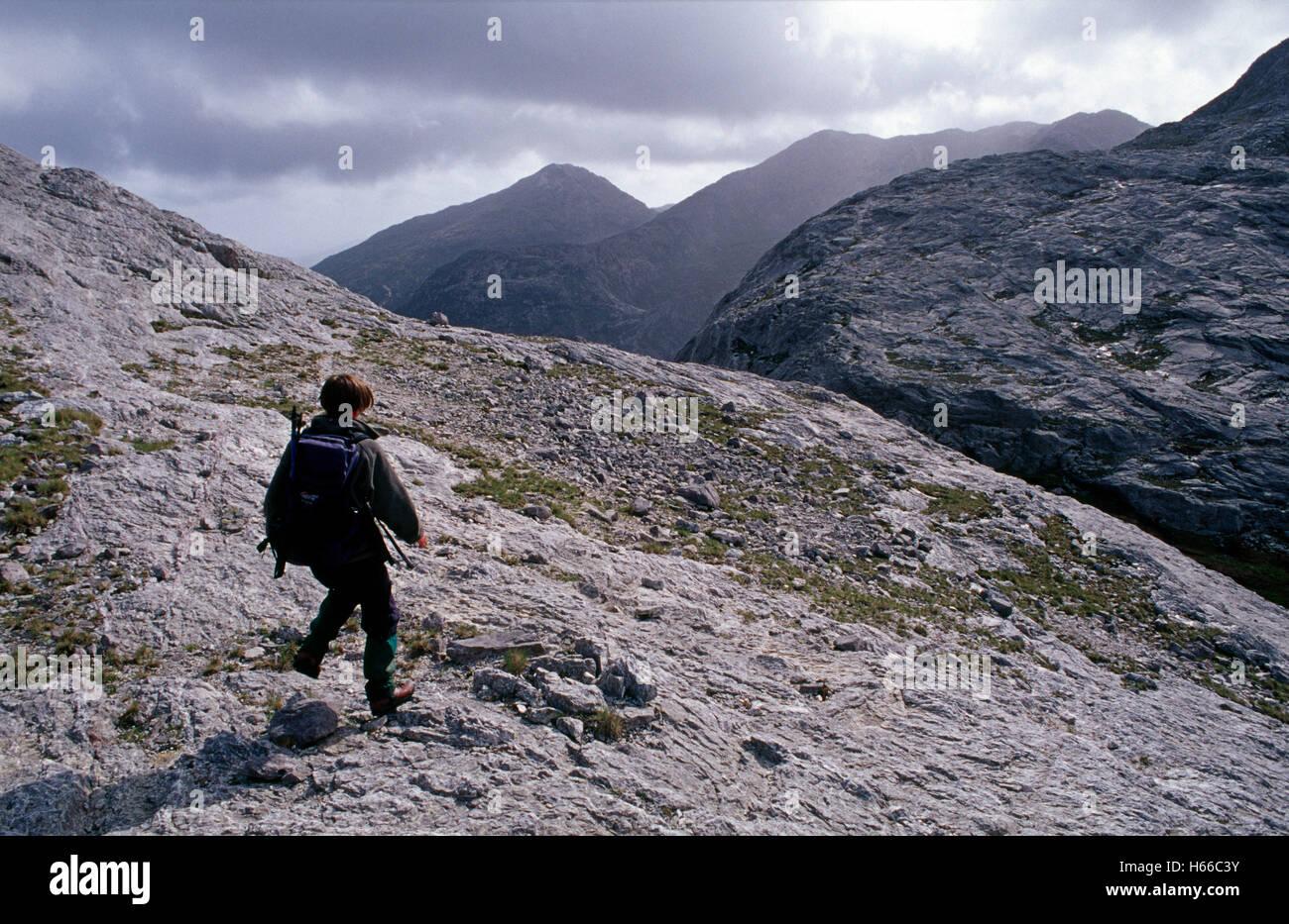 Walker in the Twelve Ben Mountains, Connemara, County Galway, Ireland. - Stock Image