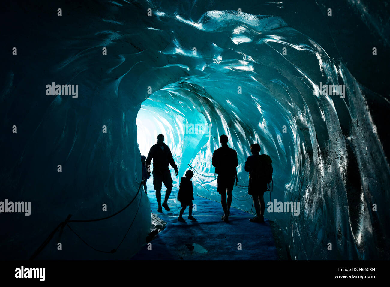 Tourists inside the ice cave in Mer de Glace glacier, Montenvers. Chamonix Valley, French Alps, France. - Stock Image