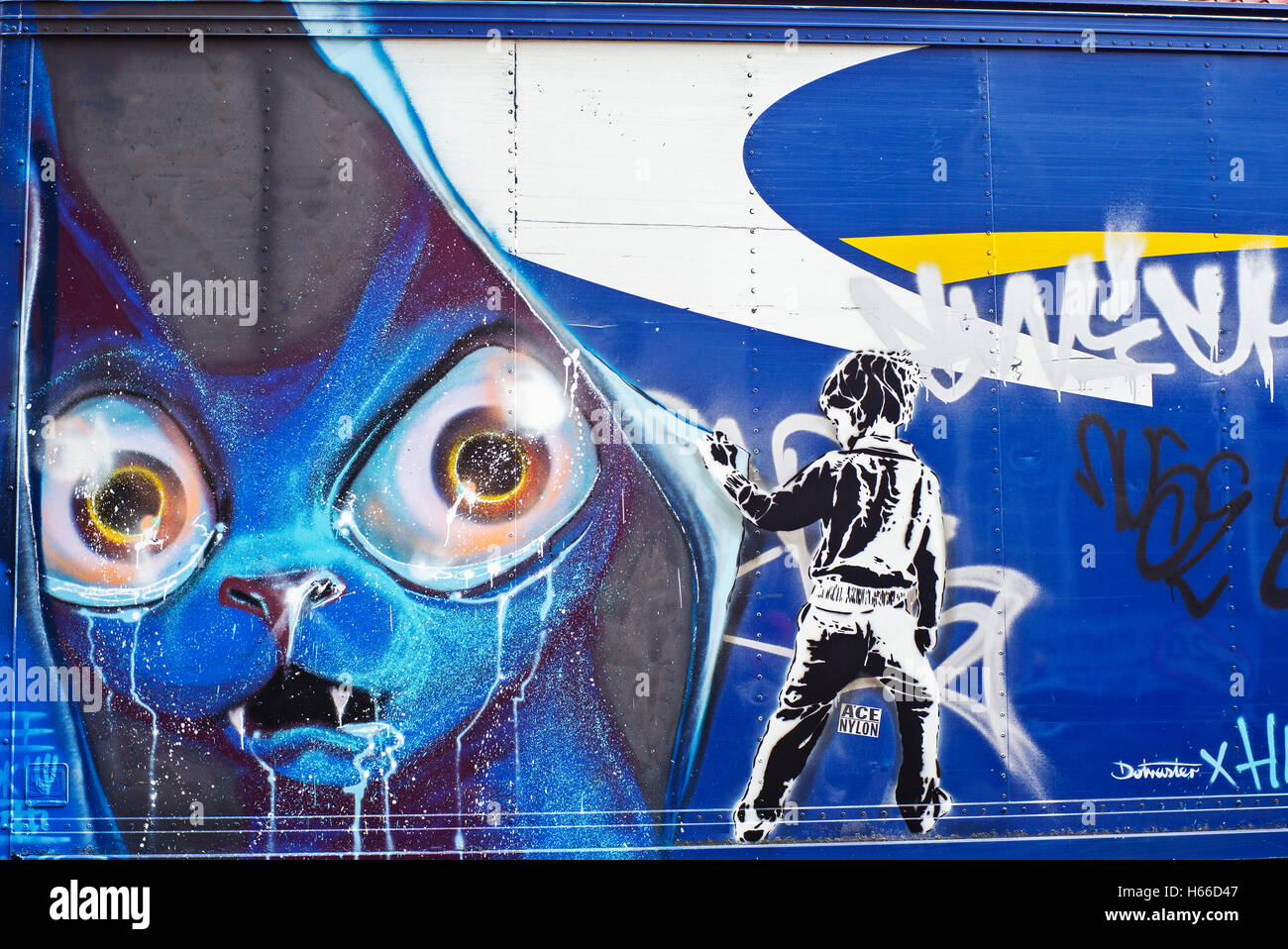 Graffiti on a goods Van, blue cat behind curtain child pulls curtain back in a reveal - Stock Image
