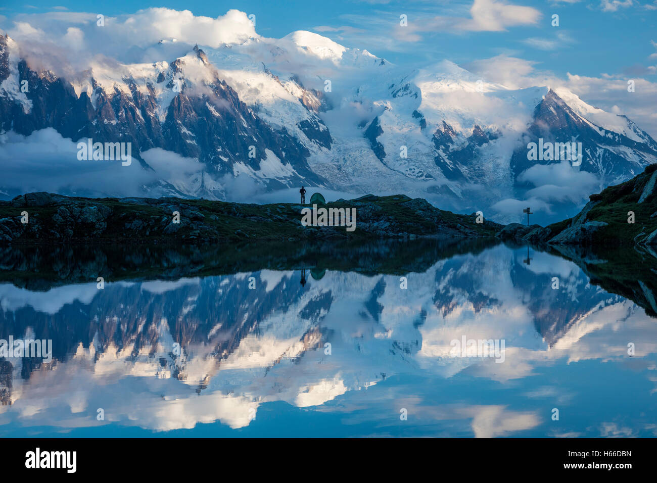 Hikers and the Mont Blanc massif reflected in Lac des Cheserys. Chamonix Valley, French Alps, France. Stock Photo