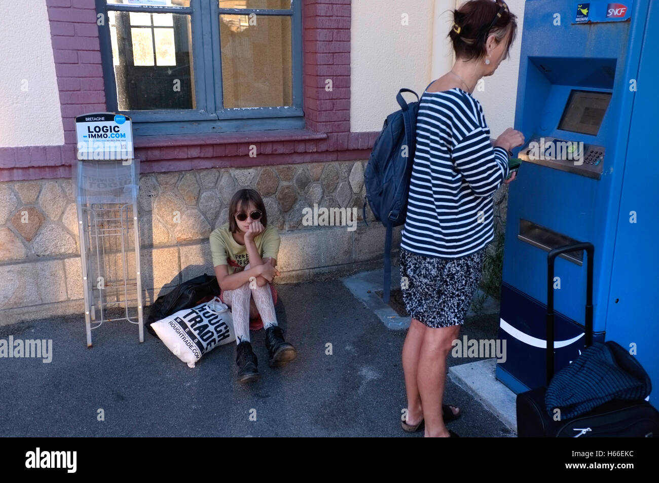 A mother buys a train ticket for whilst her daughter sits bored. - Stock Image