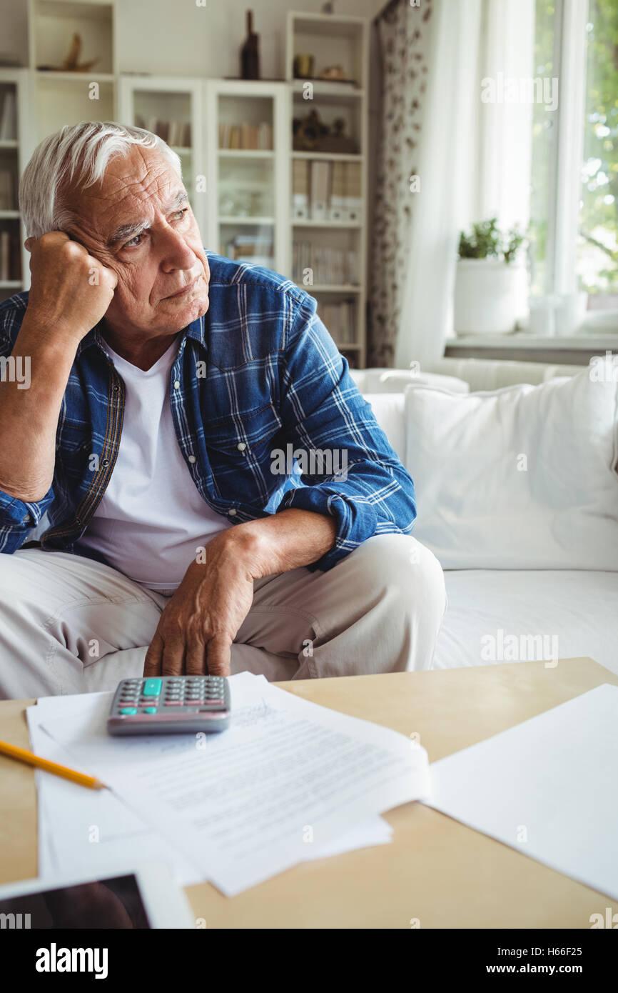 Worried senior man sitting on a sofa - Stock Image