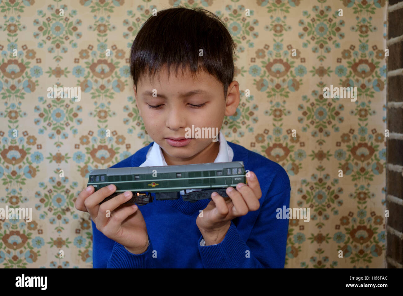 young boy playing with electric train set in a 1970s setting england uk Stock Photo