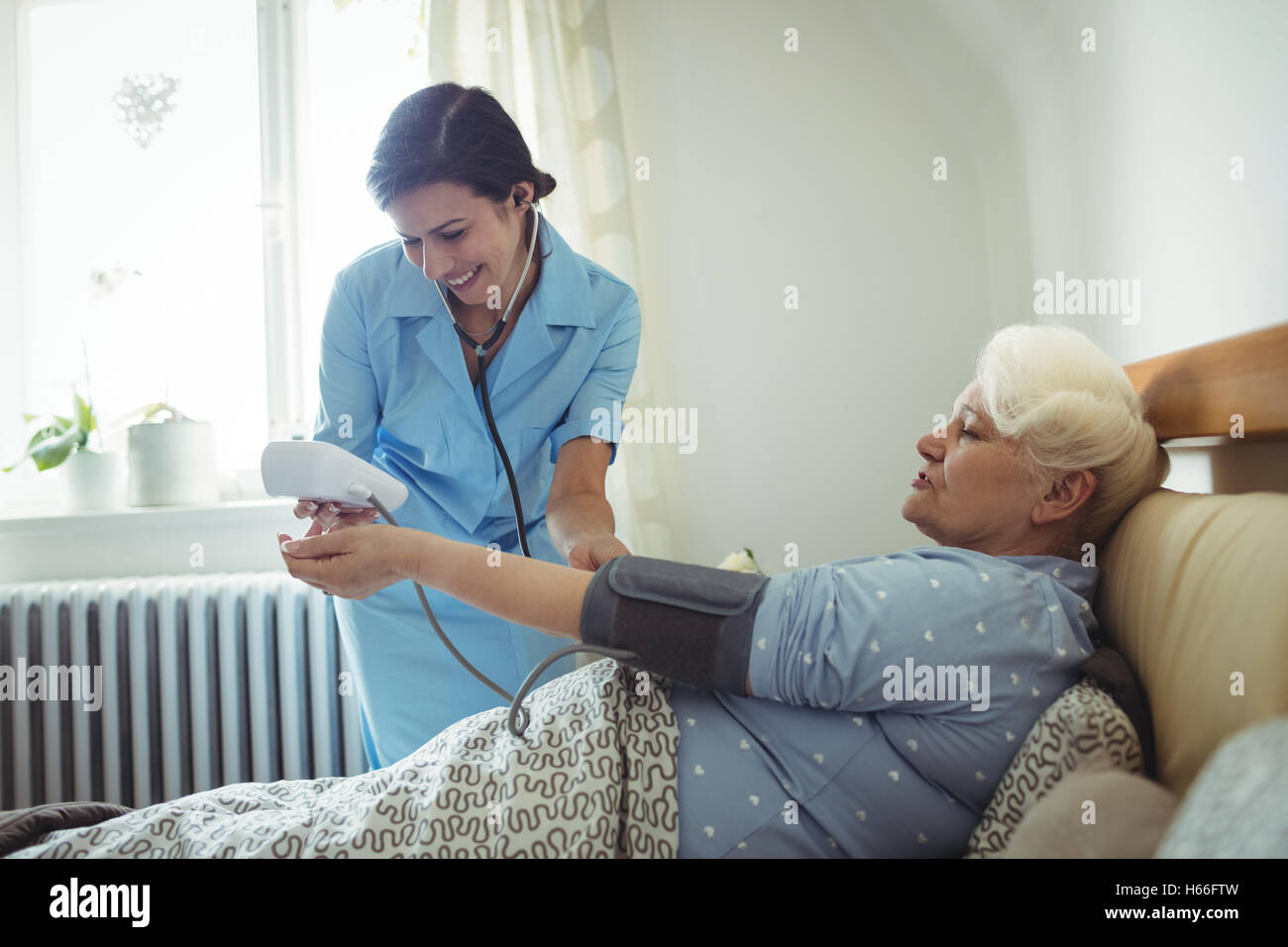 Nurse checking blood pressure of senior woman - Stock Image