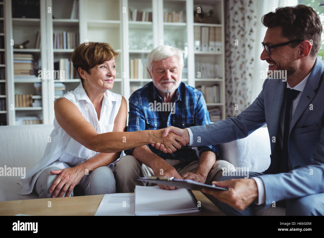 Financial advisor shaking hands with senior woman - Stock Image