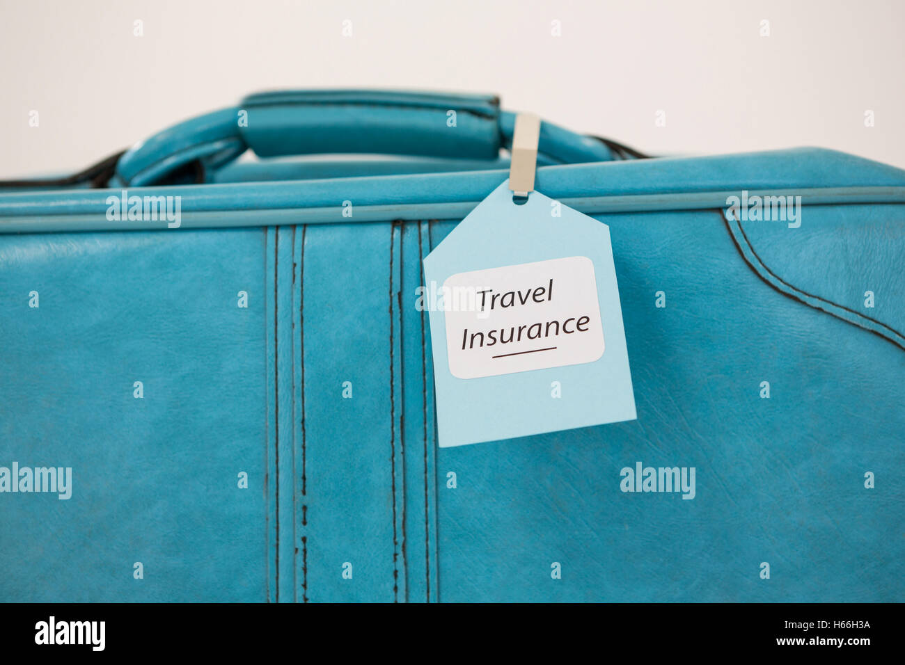 Travel insurance label tied to a suitcase - Stock Image