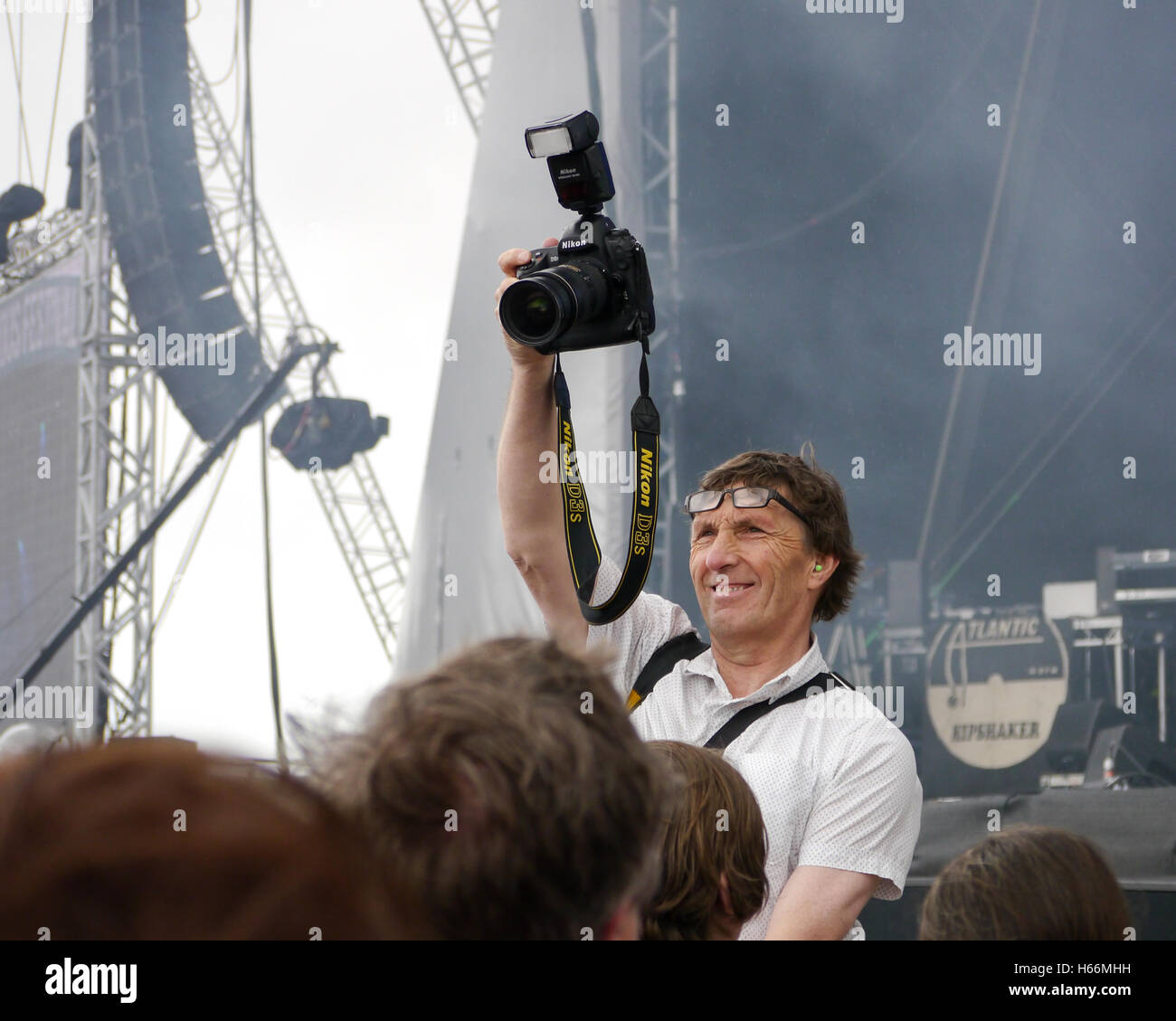 A photographer takes a crowd shot at a music festival - Stock Image