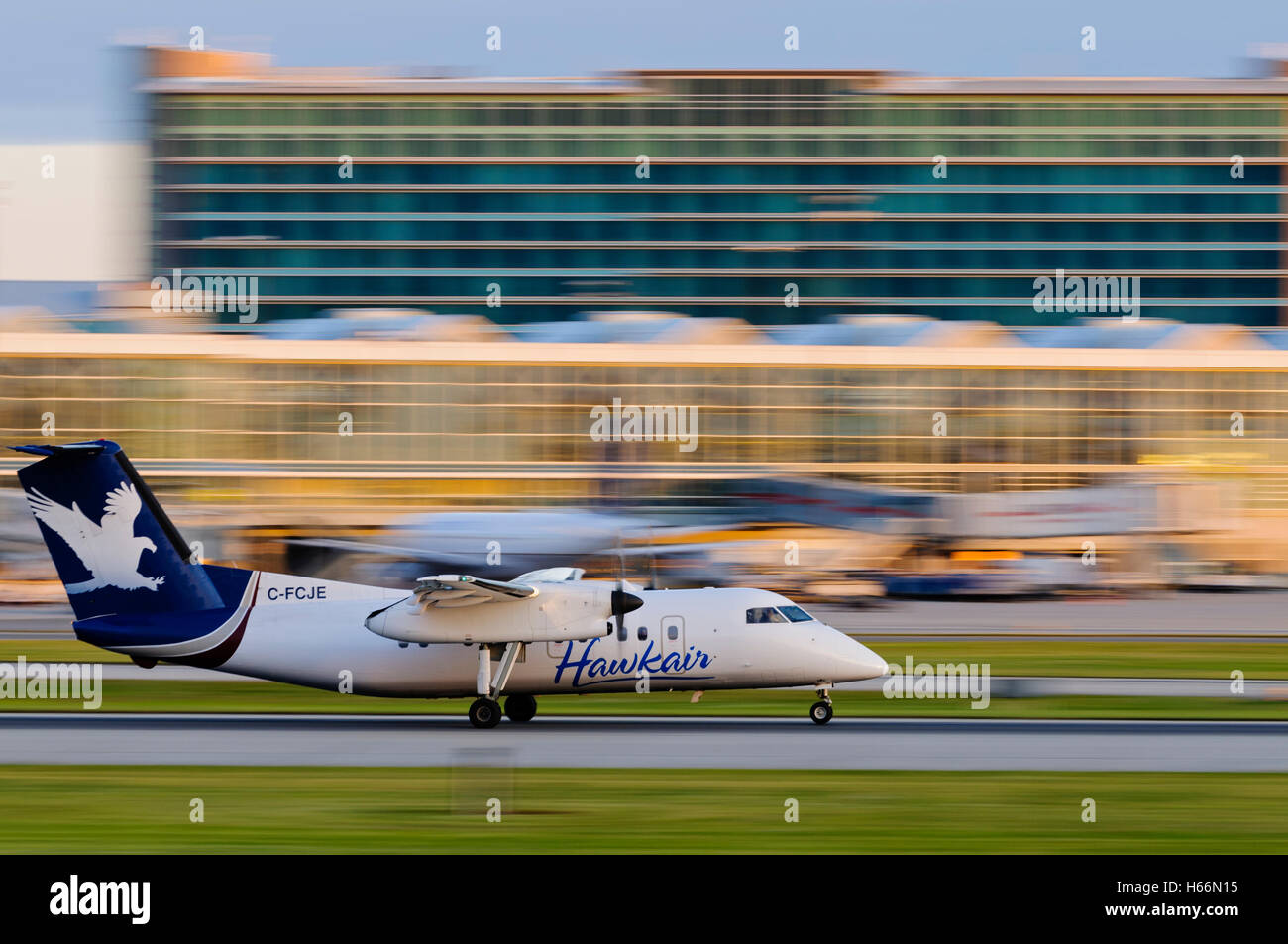 A Hawkair Aviation Dash 8 (C-FCJE) twin engine turboprop regional airliner lands at Vancouver International Airport, - Stock Image