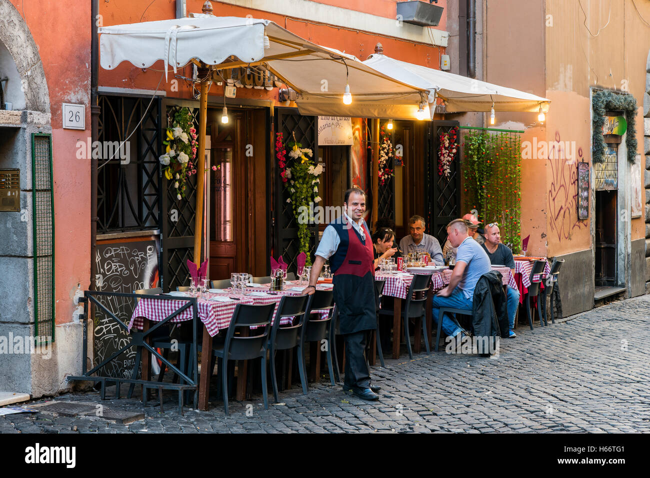 Tourists eating al fresco in a restaurant of Trastevere district, Rome, Lazio, Italy - Stock Image
