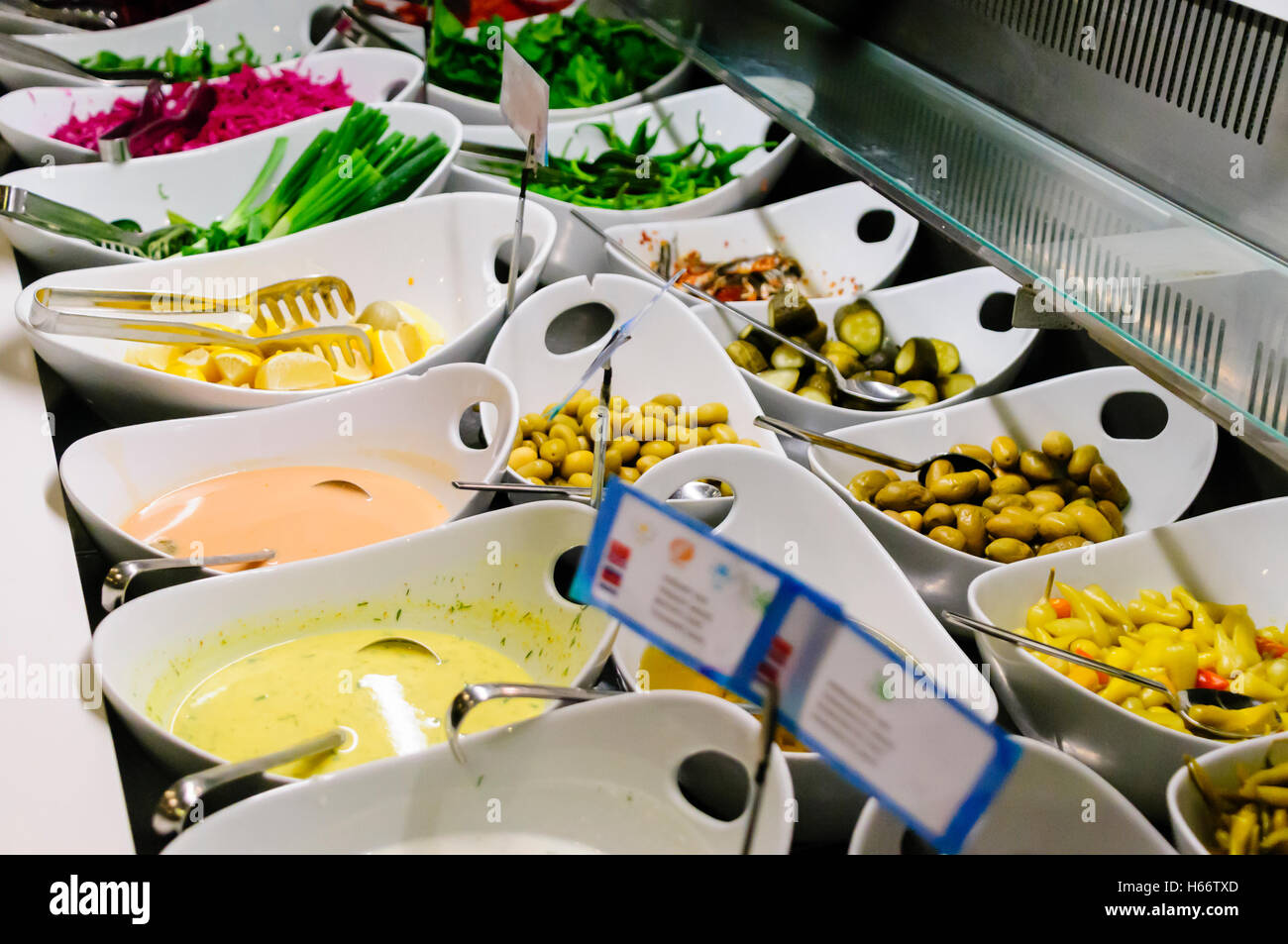 A selection of olives, chilies, sauces and garnishes at the buffet counter of a restaurant - Stock Image