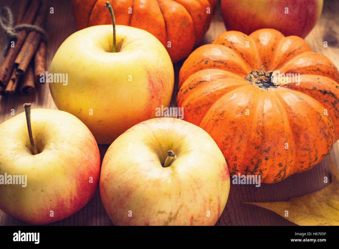 Autumn harvest: apples, pumpkins and bunch of cinnamon sticks on wooden table. Seasonal harvest. Toned image Stock Photo