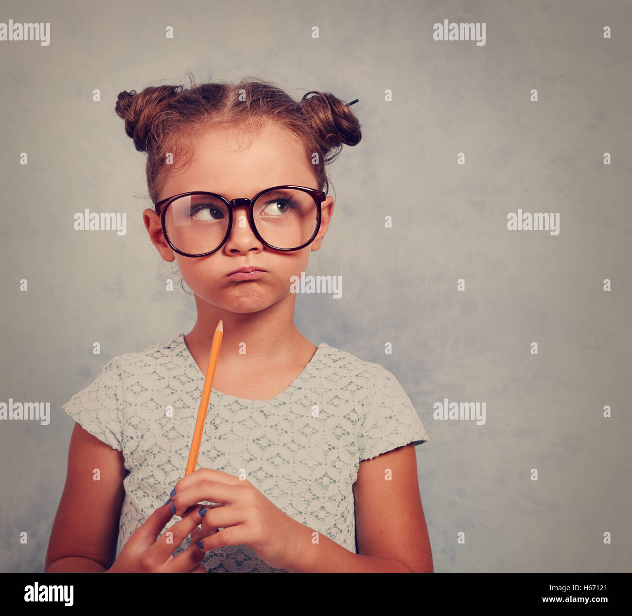 Thinking grimacing kid girl in glasses looking and holding pencil in hand on blue background with empty copy space. - Stock Image