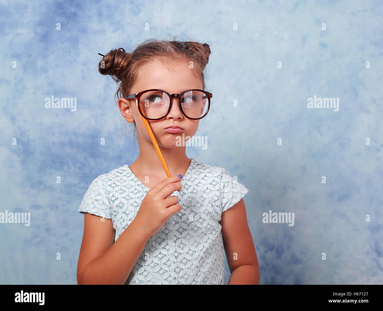 Thinking grimacing kid girl in glasses looking up and have an idea, holding pencil in hand on blue background with - Stock Image