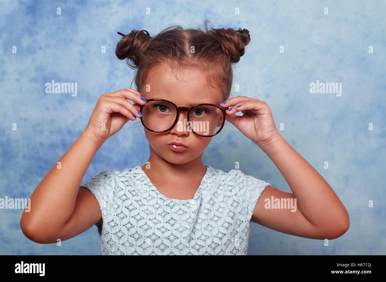 Serious angry kid girl with modern hair style in fashion glasses looking and holding the eyeglasses with empty copy - Stock Image