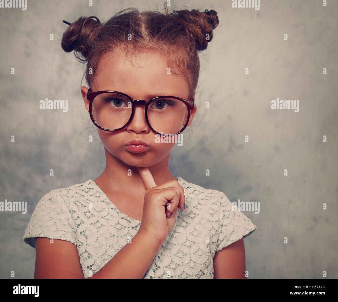 Serious angry kid girl with modern hair style in fashion glasses looking with finger under face with empty copy - Stock Image