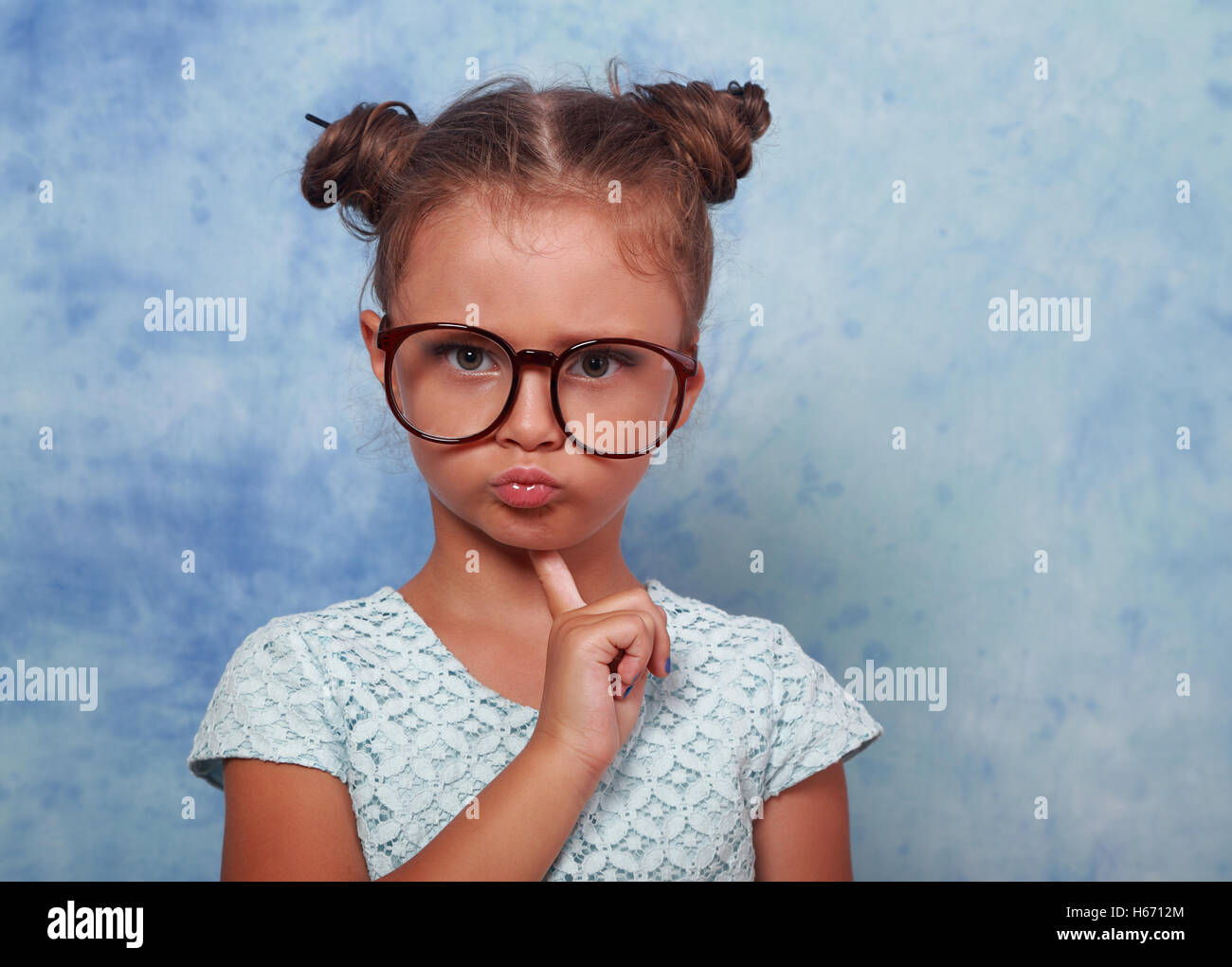 Serious angry kid girl with modern hair style in fashion glasses looking with finger under face on blue background - Stock Image