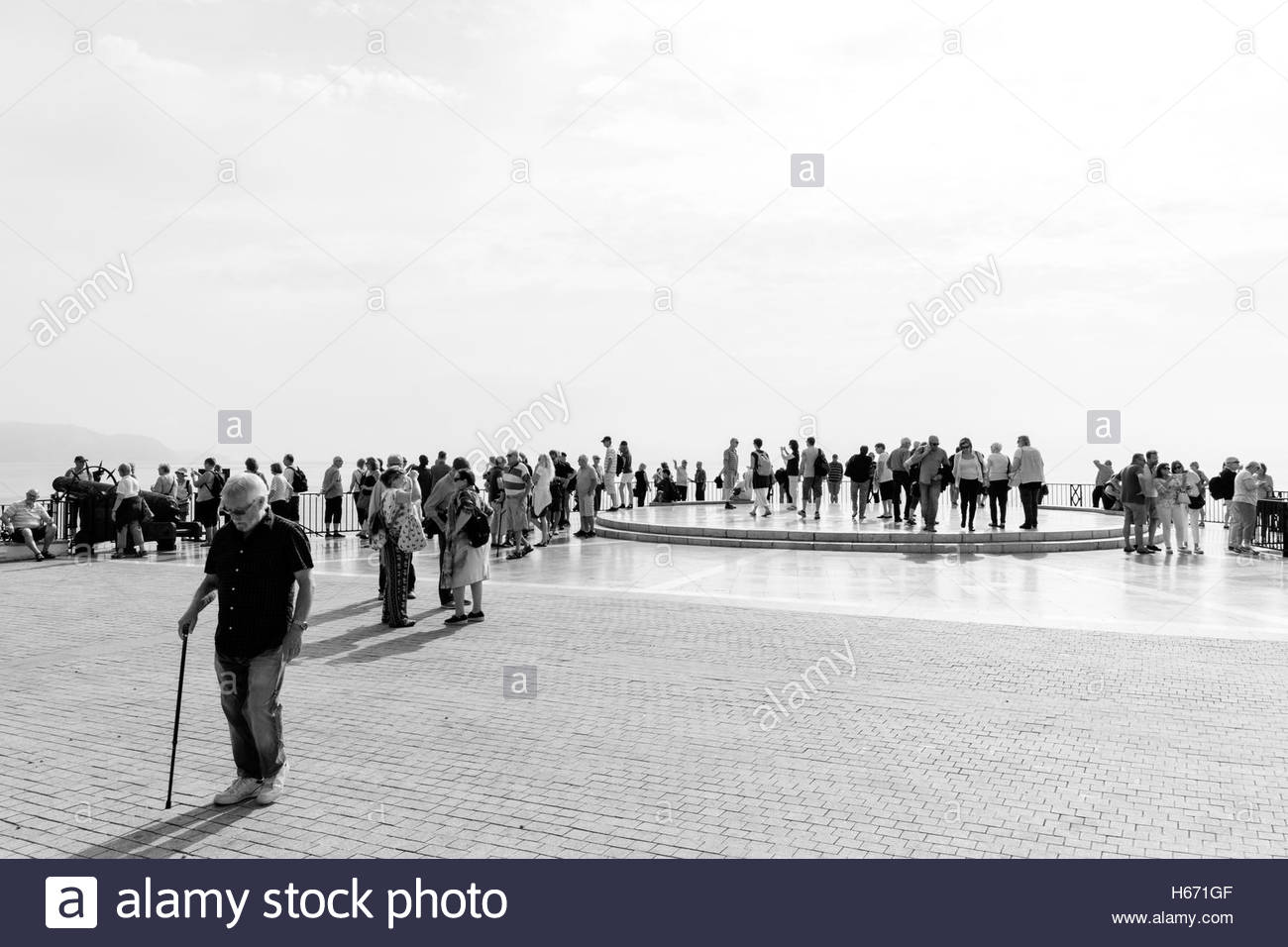 crowds of  tourists gather on the Balcón de Europa in Nerja Spain. Taken in black and white Stock Photo