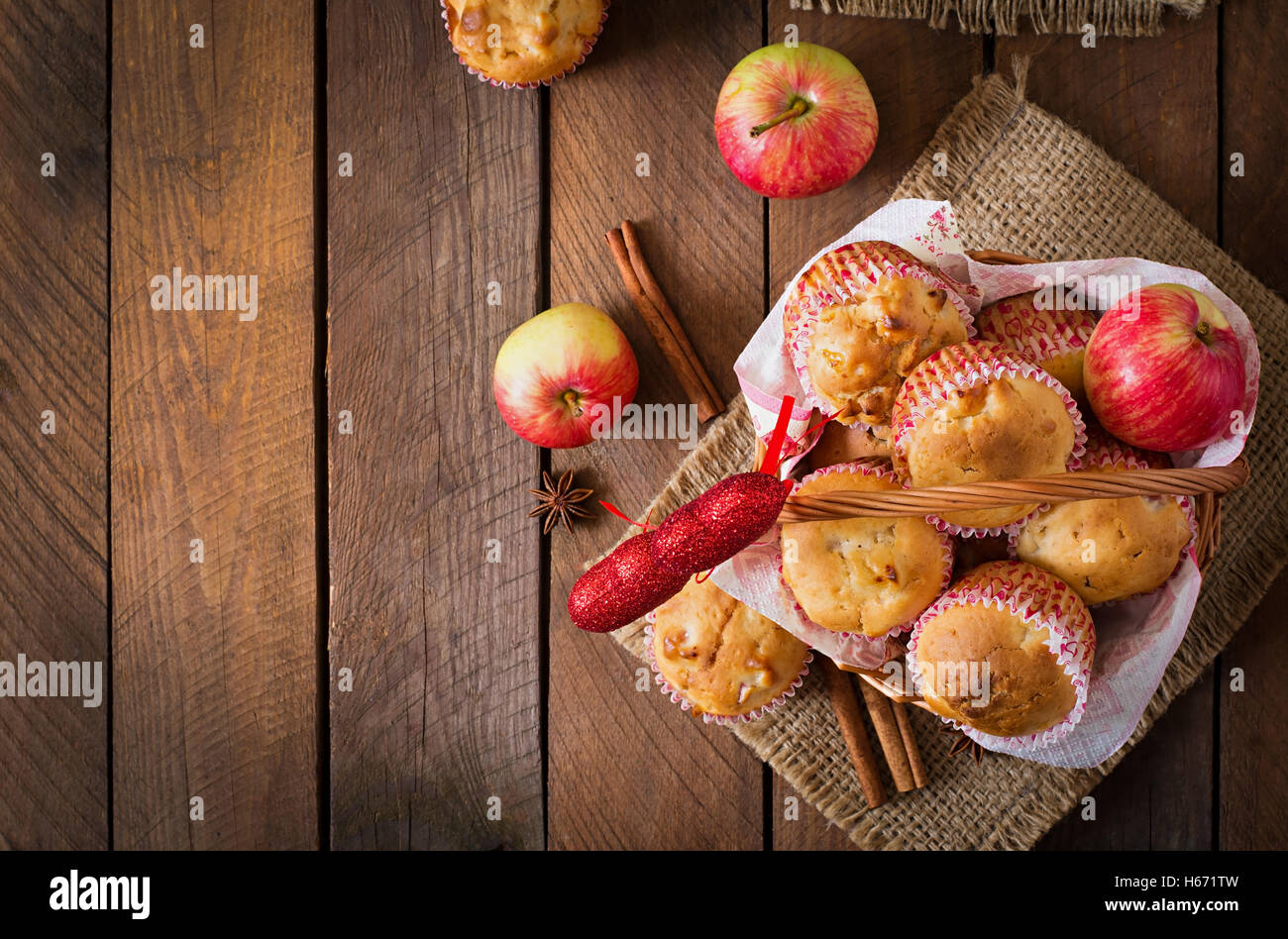 Tasty muffins with apple and cinnamon in basket on a wooden background. Top view - Stock Image