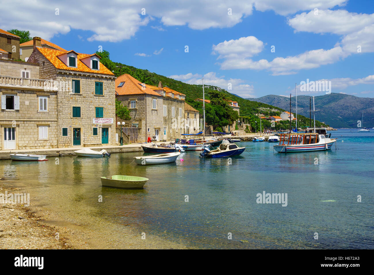 SUDURAD, CROATIA - JUNE 27, 2015: Scene of the fishing port, with boats, locals and tourists, in the village Sudurad, - Stock Image