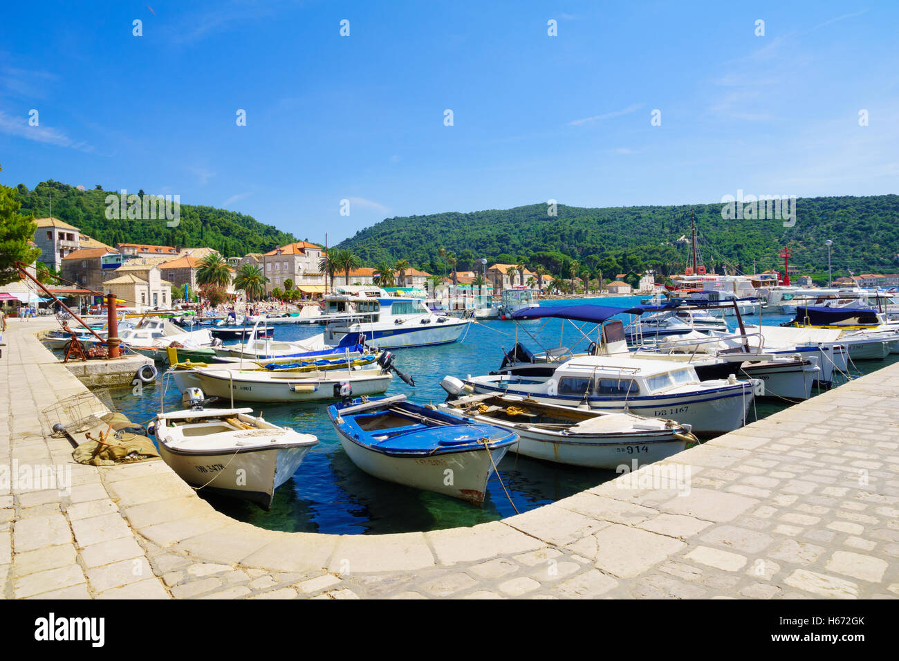 LOPUD, CROATIA - JUNE 27, 2015: Scene of the fishing port and the beach, with boats, locals and tourists, in the - Stock Image