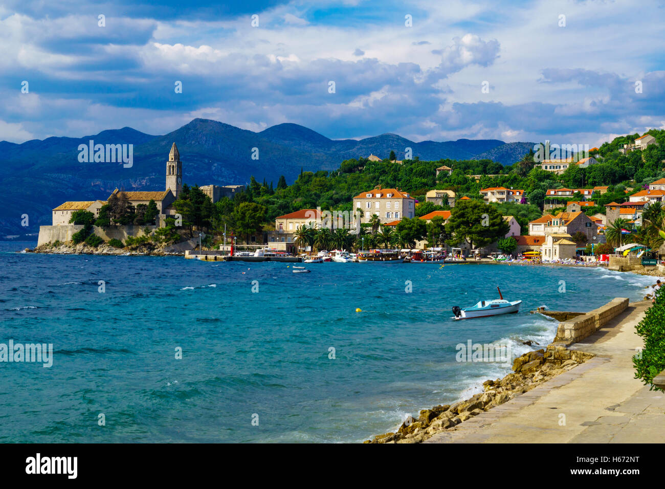 LOPUD, CROATIA - JUNE 27, 2015: Scene of the fishing port and the beach, with the Franciscan Monastery, boats, locals - Stock Image