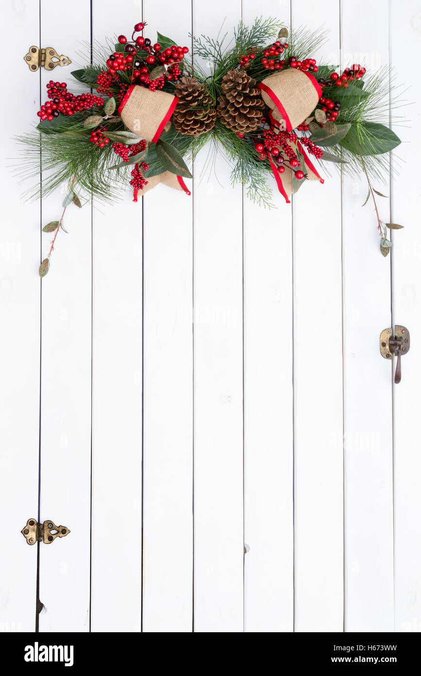 White Barn Door With A Festive Red And Burlap Rustic Christmas Decoration Berries Green Foliage Hanging At The Top