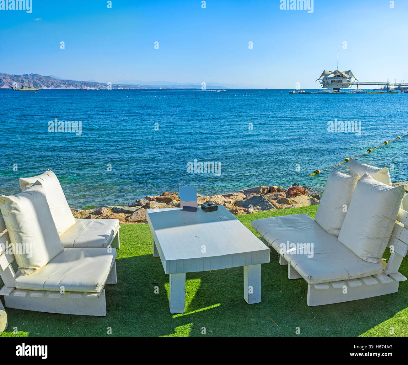 The cozy white benches in the beach cafe on the seashore with the view on the dive station, Eilat, Israel. Stock Photo