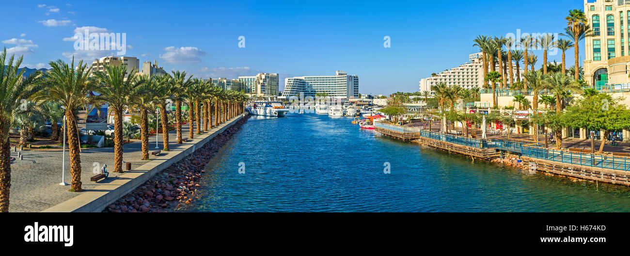 The entrance to marina, surrounded by promenades with palms, cafes, restaurants and shopping centers, Eilat - Stock Image
