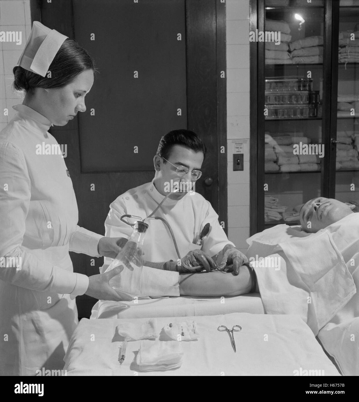 Nurse Assisting Doctor with Blood Transfusion, Fritz Henle for Office of War Information, November 1942 - Stock Image