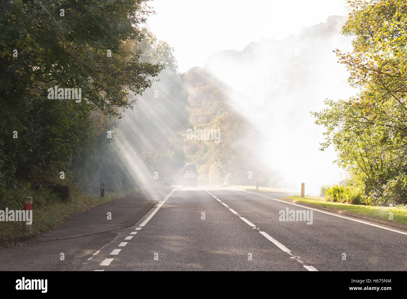 smoke from bonfire burning close to main road drifting across the road and reducing visibility - Stock Image
