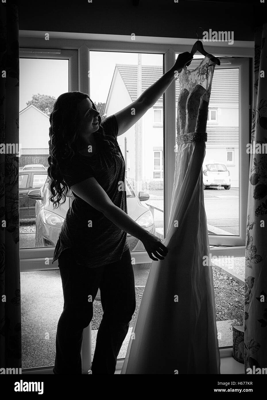 Bride getting ready for her wedding, holding up her dress and looking at it. - Stock Image