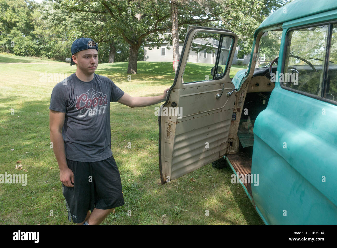 Boy age 17 waiting to enter an antique 1956 Chevy Suburban Carryall truck, still used for chores. Clitherall Minnesota - Stock Image